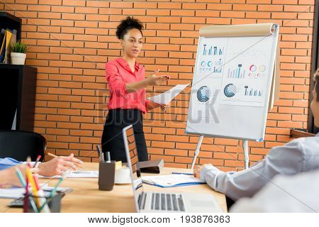 Businesswoman as a meeting leader asking her colleague for an opinion while making a presentation