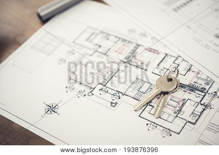 House keys on blueprint paper - properties and real estate concept
