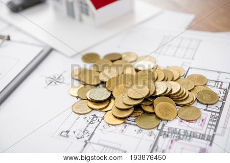 Money on blueprint paper with blurred house model in background - real estate loan and financial concepts