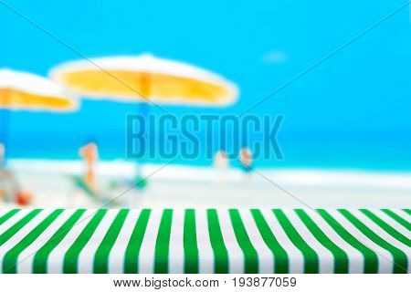 Table top covered with striped tablecloth on blurred summer beach background - can be used for display or montage your products