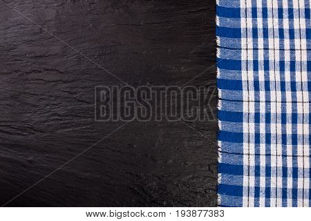 blue checkered tablecloth on the black stone table with copy space for your text. Top view.