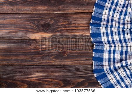 blue checkered tablecloth on the black wooden table with copy space for your text. Top view.