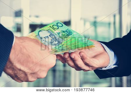 Hands of businessmen passing money Australia dollar (AUD) banknotes