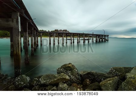 Wooden bridge on silky sea with silky rain clouds in rainy day