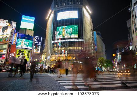 Tokyo, Japan - 27 June 2016: Slow shutter speed night shot of pedestrians crossing the street at the Shibuya Crossing intersection. In Tokyo, Japan.