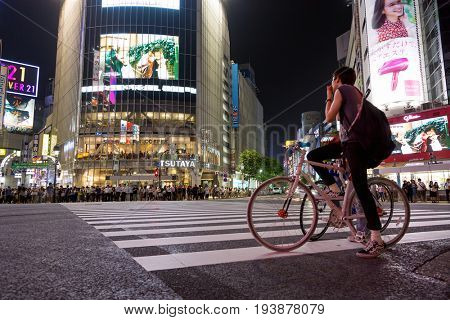 Tokyo, Japan - 27 June 2016: Cyclists and pedestrians are waiting to cross the street at the Shibuya Crossing intersection. Evening shot in Tokyo, Japan.