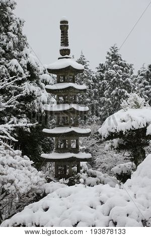 Garden feature in the shape of a five-tiered pagoda covered with snow in a Japanese garden after a snowfall.