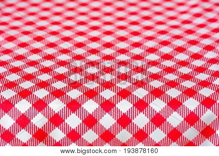 Table covered with red checkered picnic tablecloth - can be used as background for montage food and products