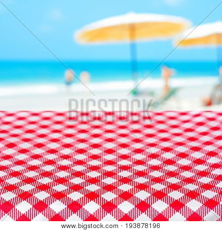 Red checkered table cloth on blurred beach background summer holiday beach picnic concept - can be used for display or montage your products