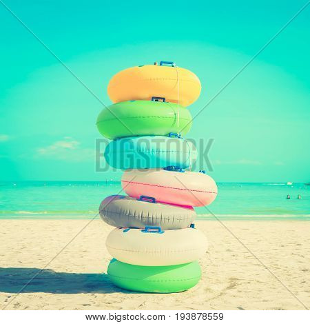 Stack of colorful rubber rings (or swim rings) on white sand beach vintange tone - summer holiday concept