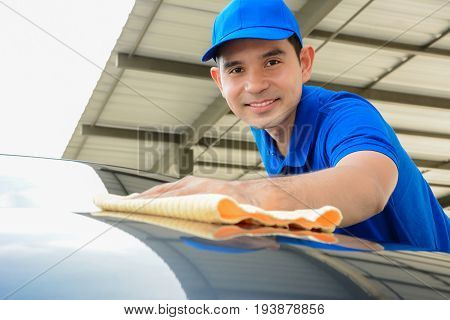 A man polishing car with microfiber cloth car detailing or valeting concept - face focused
