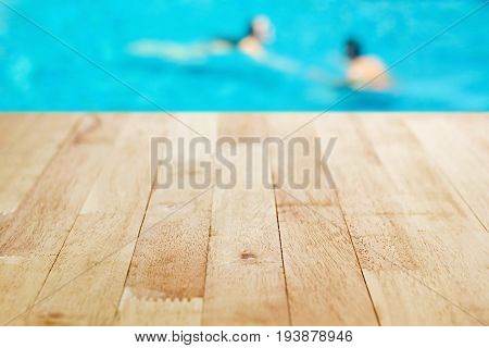 Wood table top on blurred background of swimming pool with few people