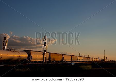 Train Passing Signal Towers in a Golden Sunset
