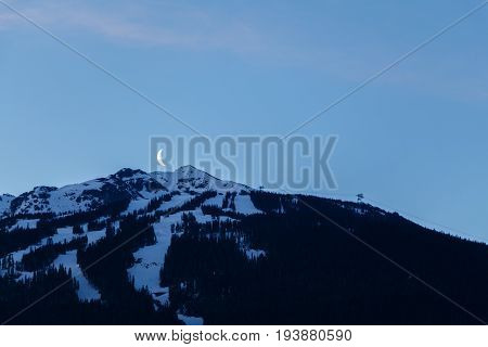 The moon rising over Blackcomb Peak at dawn. Taken in  Whistler, Canada.