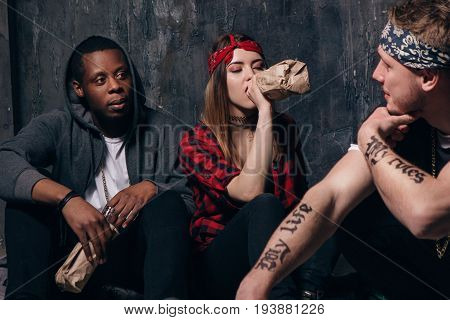 Group of alcoholic young people on night party. Youth addiction problem. Tired drunk caucasian girl drink alcohol from bottle, sad guys with tattoo sits near . Students lifestyle