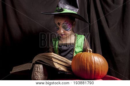 Little cute girl costumed as a witch reads the Book of Spells. Studio take