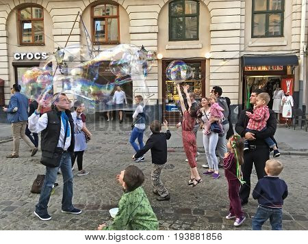 LVIV UKRAINE - MAY 06: Entertainment for children - A man blows bubbles for children in the center of Lviv on May 06 2017 in Lvov Ukraine