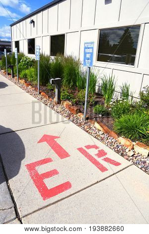 Emergency room directional sign on a hospital sidewalk