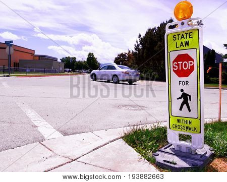 Temporary crosswalk stop sign at a street intersection with a car driving through