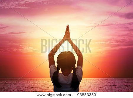 Close up Silhouette of A young girl practicing Yoga vrikshasana tree pose on tropical beach with sunset sky background watching the sunset background and copy space. Yoga for kids concept.