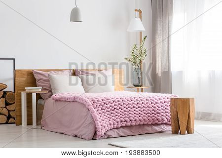 White and pink design of cozy bedroom with wooden bed
