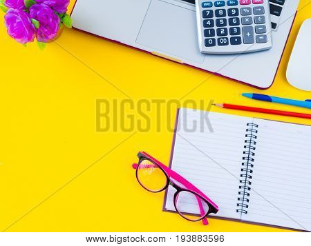 Flat lay top view office table desk frame. feminine desk workspace with office accessories including calculator mouse laptop glasses clips red pencil cutter note book blue pen and pink flower on yellow background. Education and business concept.