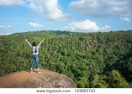 Joyful Young Asian girl holding hands and breathing fresh air standing outdoor on cliff. Healthy active lifestyle concept Copy space. Pha Koo Rak Phu Hin Rong Kla national park PhitsanulokThailand