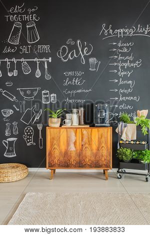 Chalk drawings on kitchen wall and coffee machine on cupboard