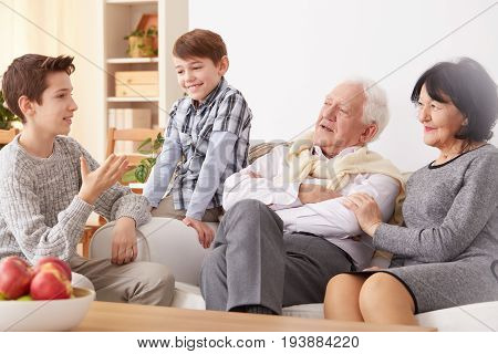 Young grandsons spending lovely time with beautiful grandparents