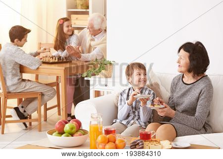 Beautiful grandmother and her happy grandson eating delicious homemade cake