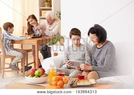 Young boy and his beautiful grandmother using modern tablet