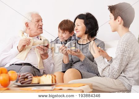 Happy grandparents eating tasty homemade cake with their lovely grandsons