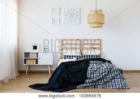 Black and white modern bedroom with wooden bed