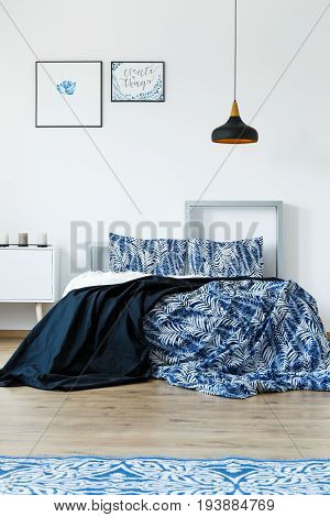 Blue and white bedding in cozy bedroom with white walls