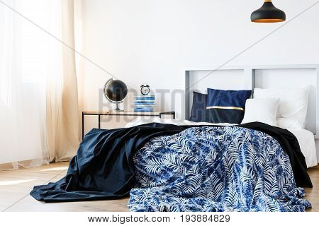 Bed with blue and white bedding and modern headboard