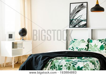 Green and white design of spacious bedroom with bed