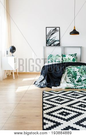 Natural style accessories in cozy white bedroom with patterned carpet