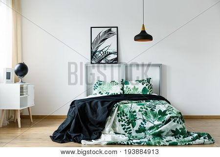 Black blanket on floral green and white bedding on bed