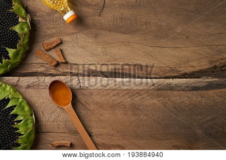 Sunflower and spoon with oil bottle with a sunflower oil on wooden rustic table. Top view copy space.