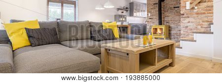 Big grey sofa with yellow accessories and wooden coffee table