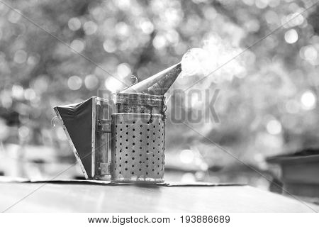 Monochrome shot of a bee smoker in apiary copyspace beekeeping honeycraft farming tool equipment concept.