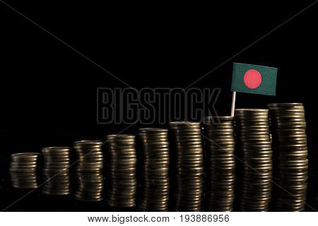 Bangladeshi Flag With Lot Of Coins Isolated On Black Background