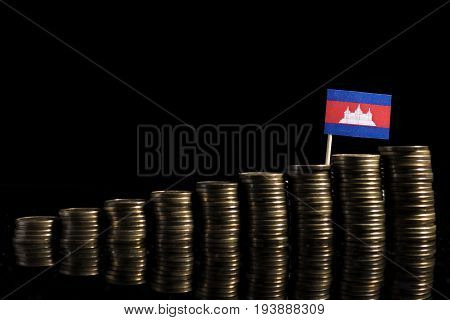 Cambodian Flag With Lot Of Coins Isolated On Black Background