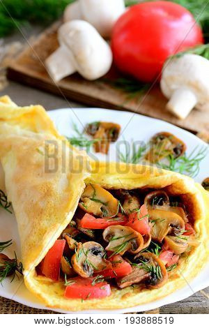 Mushroom and tomato omelet on a white plate. Egg omelet stuffed with mushrooms, tomatoes and dill. Light summer lunch or diner idea. Vertical photo