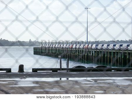 New car imports on wharf viewed through chain link fencing at Auckland New Zealand NZ