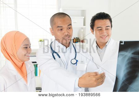 Doctors looking at x-ray scan image. Southeast Asian Muslim people.