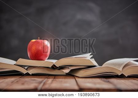 Back to school and happy time! Apple and pile of books on the desk on background of blackboard.