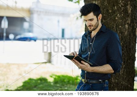 Casual young man using tablet outdoors.