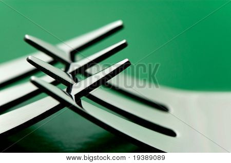 alguns garfos de talheres contra um fundo verde