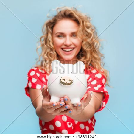 Curly haired blonde smiling girl wearing red shirt whit white dots holding porcelain pig looking at camera.